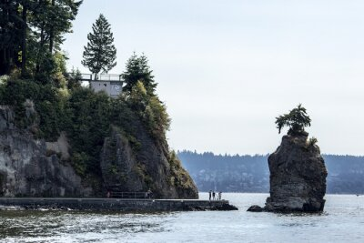 Sticker touristis at siwash rock on stanley park seawall and cliff on a sunny summer day