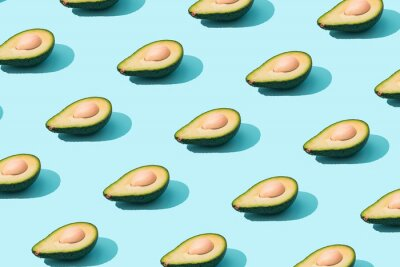 Sticker Trendy sunlight Summer pattern made with avocado fruit on bright light blue background. Minimal summer concept.