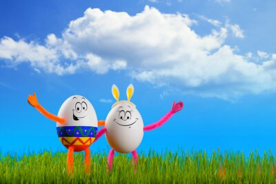 Two funny Easter eggs standing in a spring grass