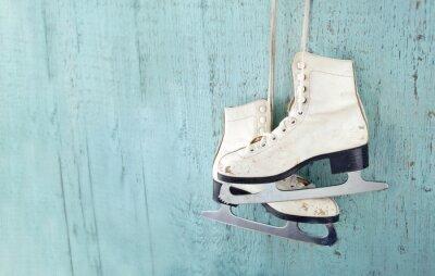 Sticker Women's ice skates hanging on blue wooden background