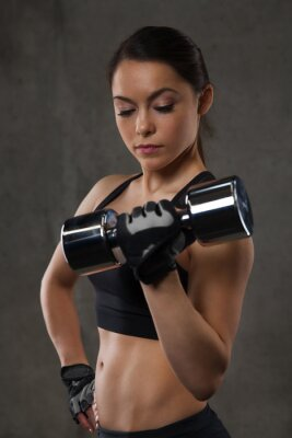 Sticker young woman flexing muscles with dumbbells in gym